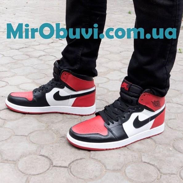 фото высоких белых с красным кроссовок Nke Air Jordan 1 на ноге.